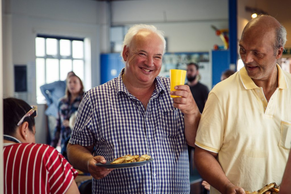 Man smiling holding a cup and plate of food.