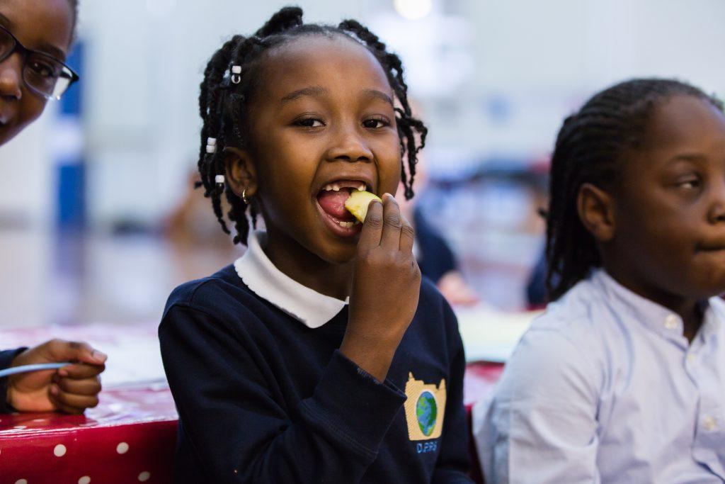 Little girl eating a slice of apple