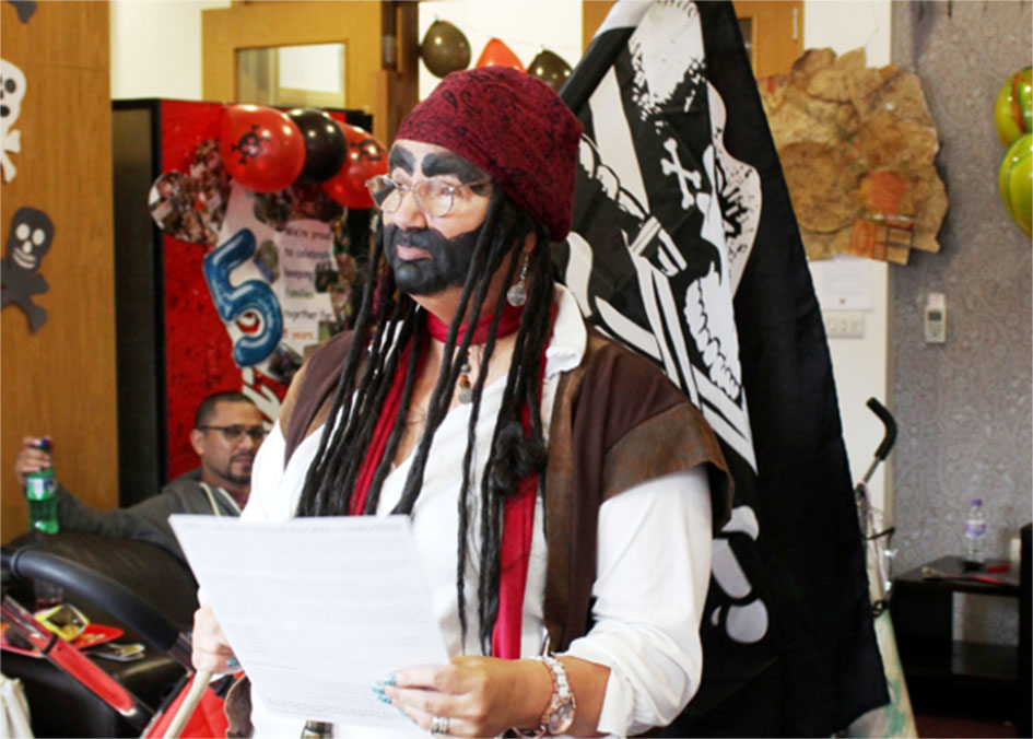 Picture of Joy dressed as a pirate leading children's games. Joy's role is supporting families with children in hospital.