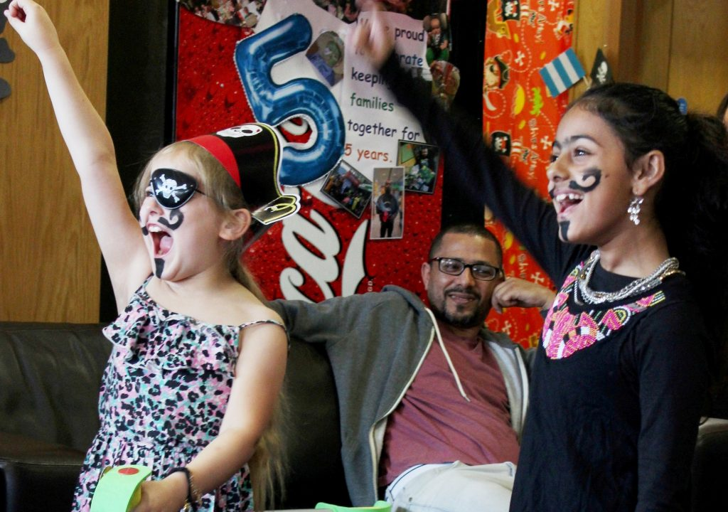 Dad Fahmi at the pirate party as his daughter Miriam plays a game with another child.  Fahmi and his family receive support from Ronald McDonald House.