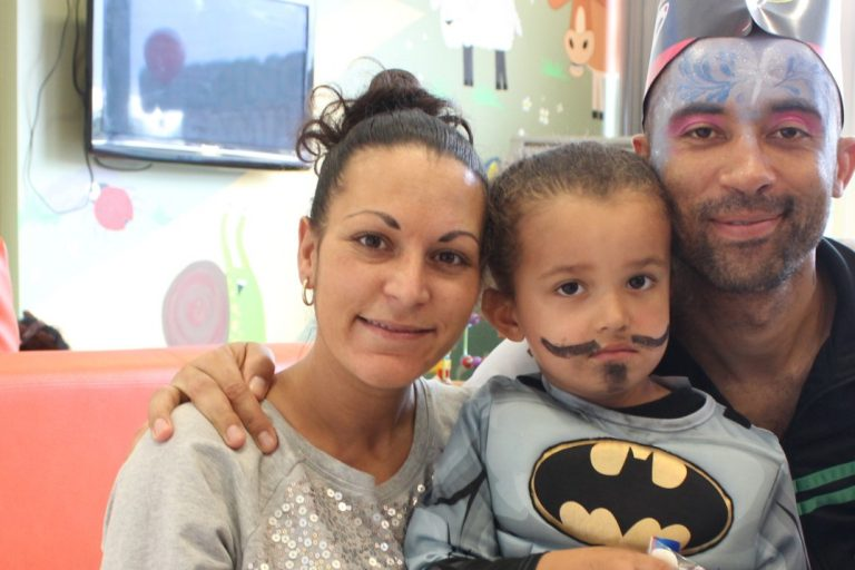 A family supported by Ronald McDonald House smile at the camera, including mum, dad and son.