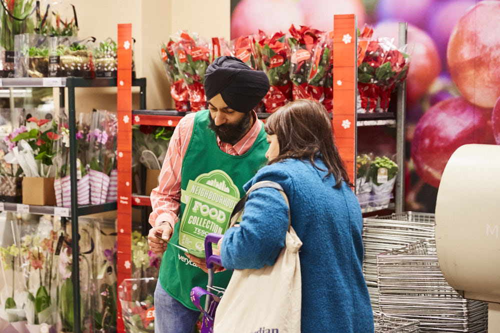 Male volunteer telling a Tesco shopper about the Food Collection in store.