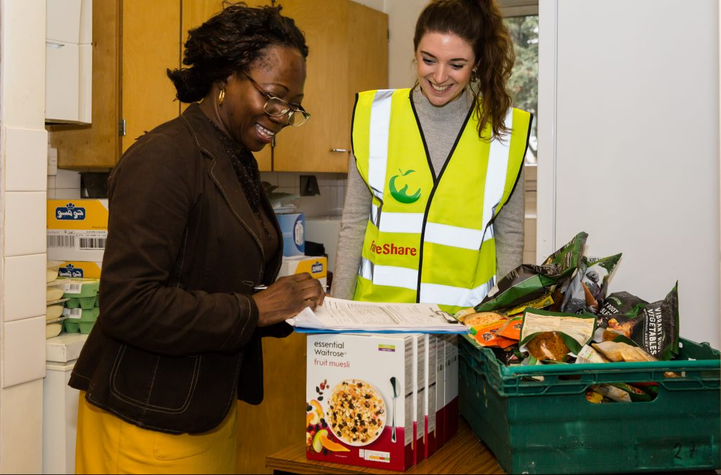 A person at a charity signs for receipt of surplus food delivered to them by a FareShare volunteer