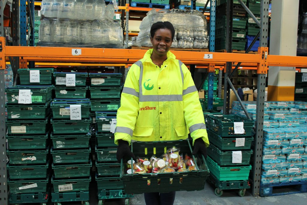 Chisom holding a tray of food volunteering in the London warehouse