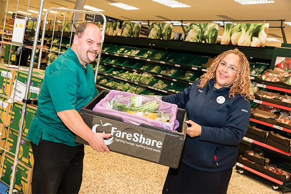 Tesco staff manager handing a man a box of surplus veg in a Tesco store