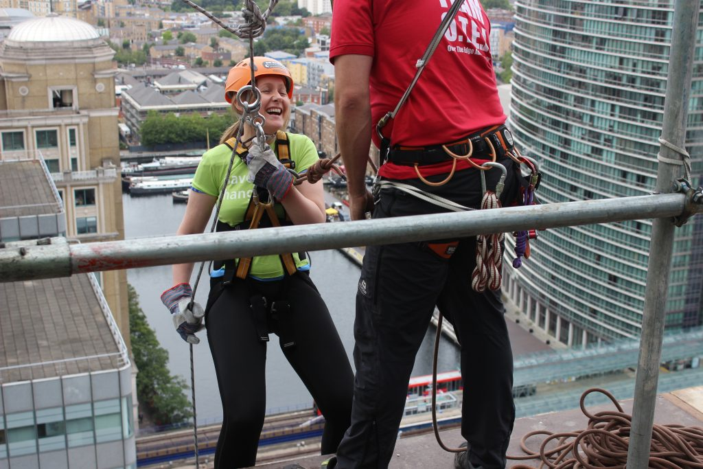 A woman abseiling down a building in Canary Wharf
