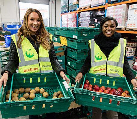 Two female volunteers in hi vis vests hold trays of surplus fruit.