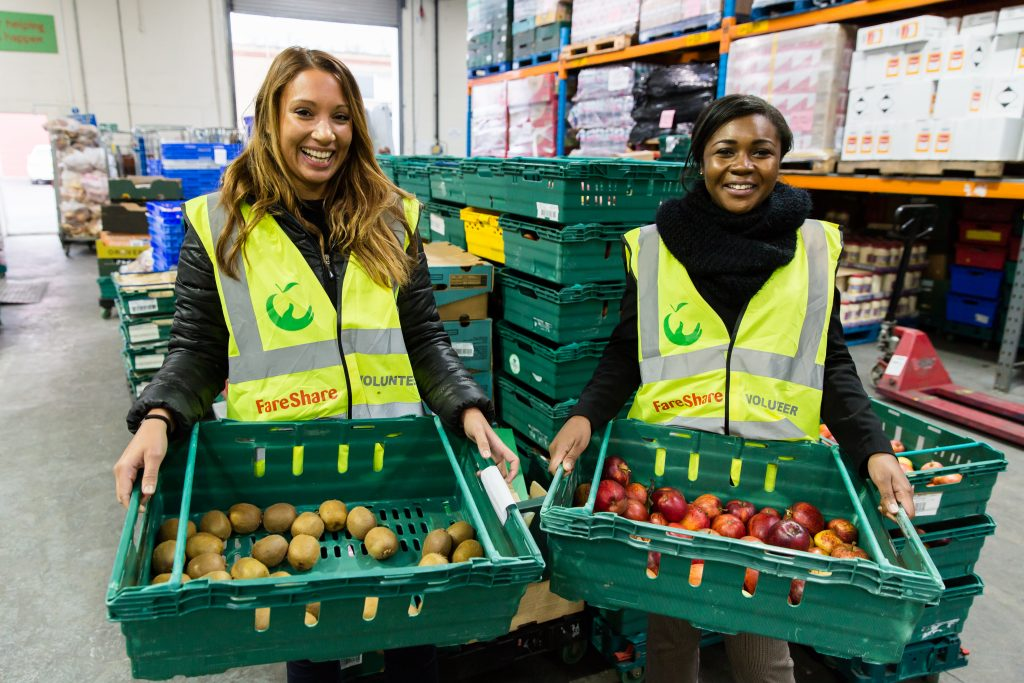 Two women in FareShare warehouse holding trays of fruit