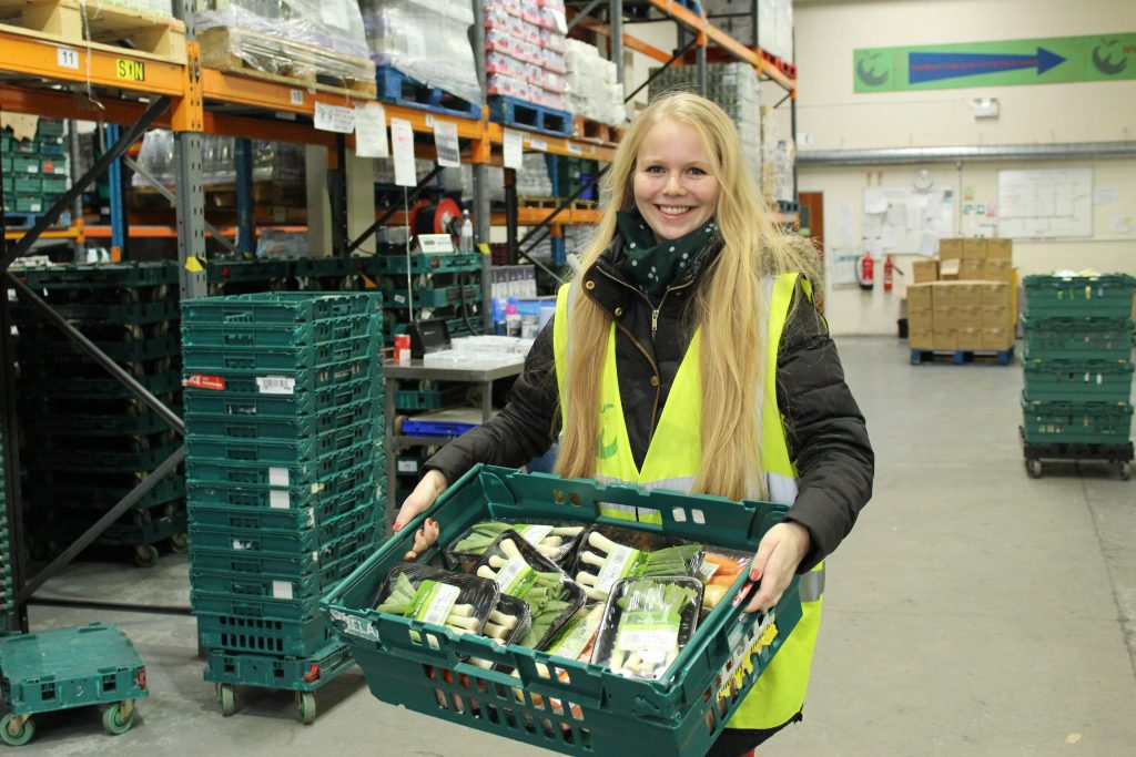 Student Viivi holds a tray of food in a warehouse.