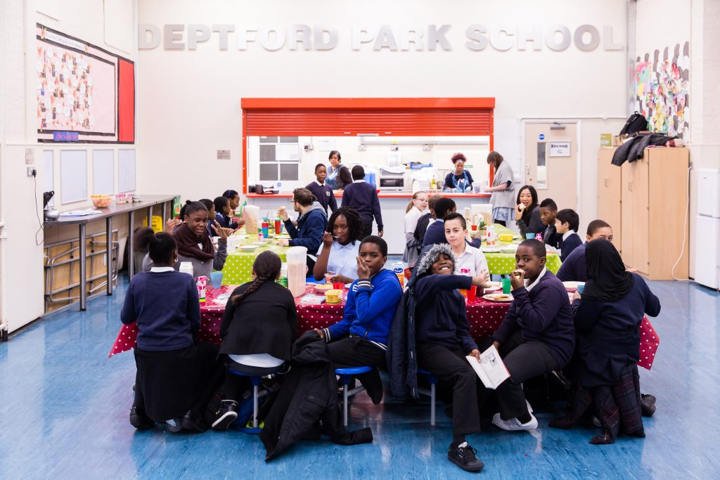 Children sitting at benches at the Deptford Park School Breakfast Club