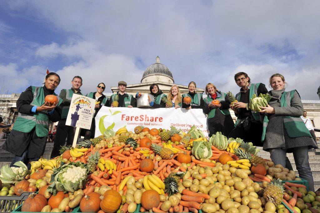 FareShare staff and volunteers stand behind a large pile of surplus vegetables with the National Gallery in the background.