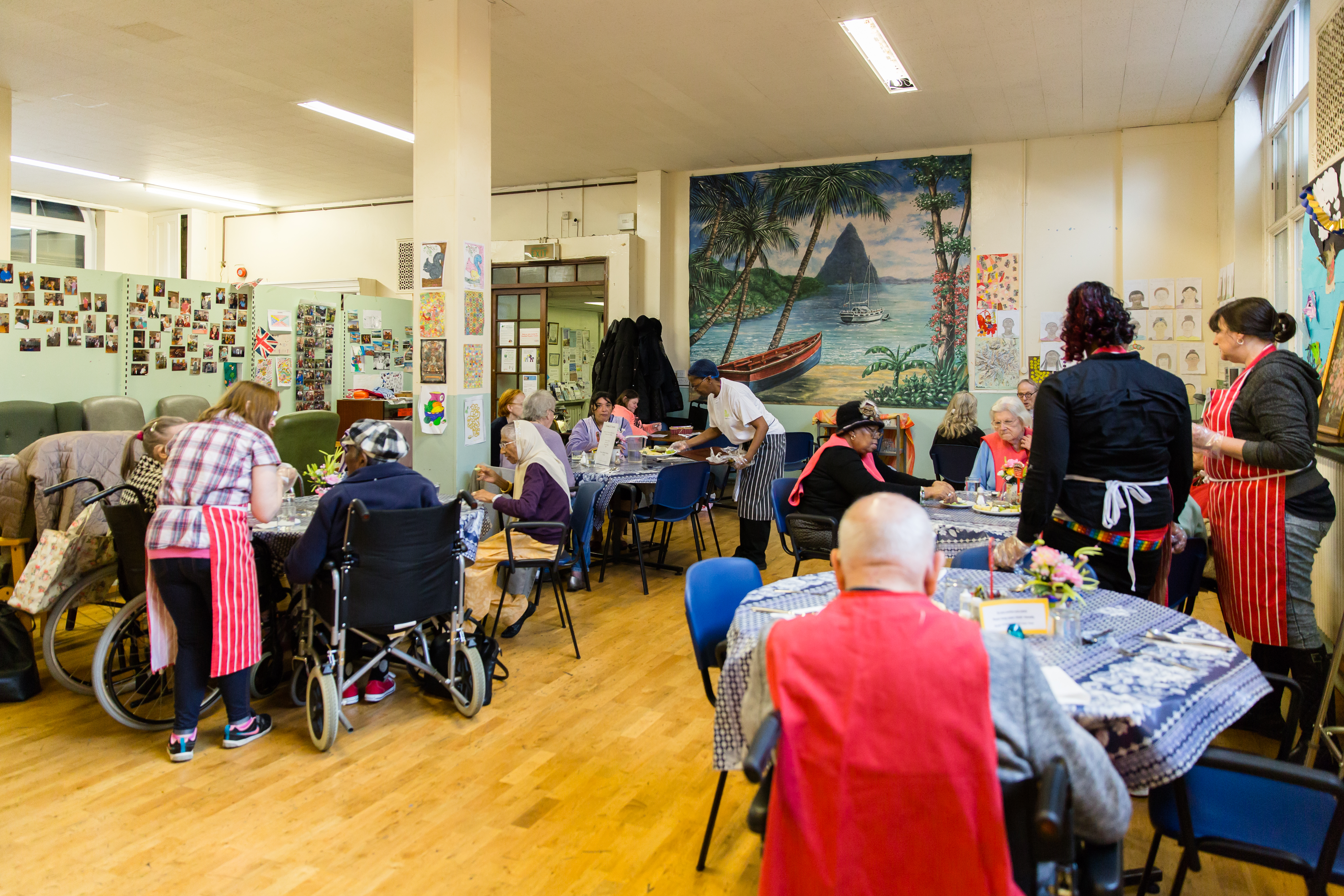 Disabled People's Contact volunteers laying up the table for 24 older people