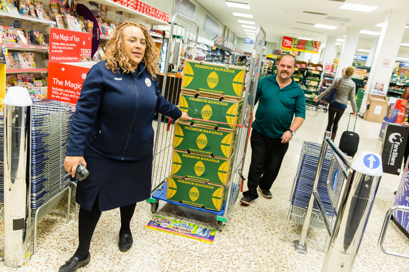 A Tesco staff member and charity volunteer pulls a trolley of surplus bananas through a Tesco store
