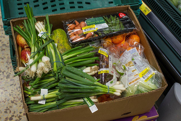 Box of surplus Tesco spring onions and carrots ready for collection by a local charity thanks to FareShare GO