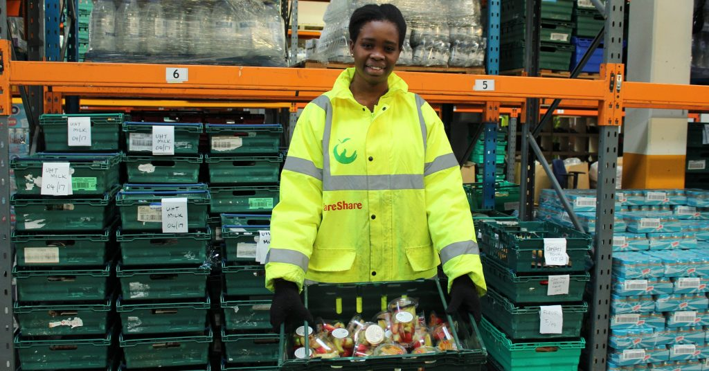 FareShare London volunteer Chisom holds a tray of surplus food saved from waste
