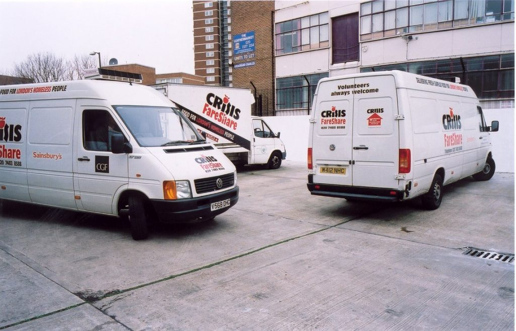 Three parked vans with the FareShare and Crisis logos on the side