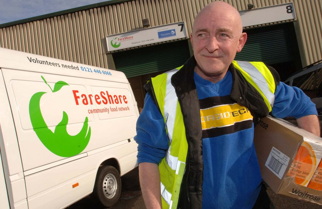 Volunteer Phil carries a box of surplus bread in front of a FareShare van