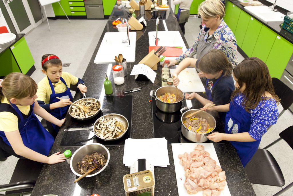 Families cooking together including three girls, one boy and a mum.