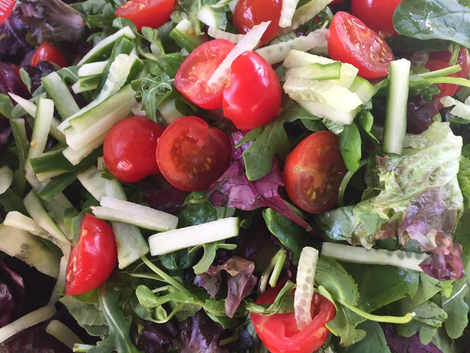Tomatoes and lettuce in a fresh salad made by FirstBite Community Food Project.