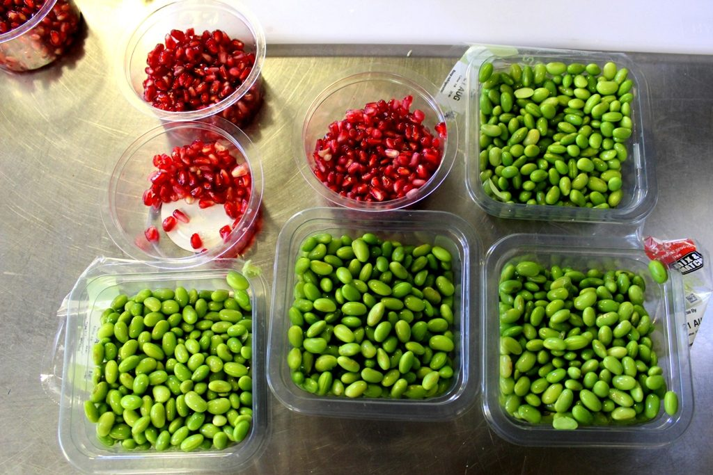 Smalls packets of edamame beans and pomegranate seeds