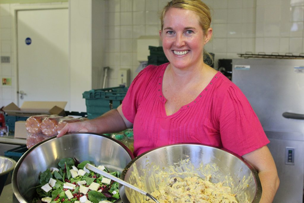 Claire, volunteer chef at Greenwich Migrant Hub, holds two cooking bowls of food as she smiles to the camera. One contains salad and one coronation chicken.