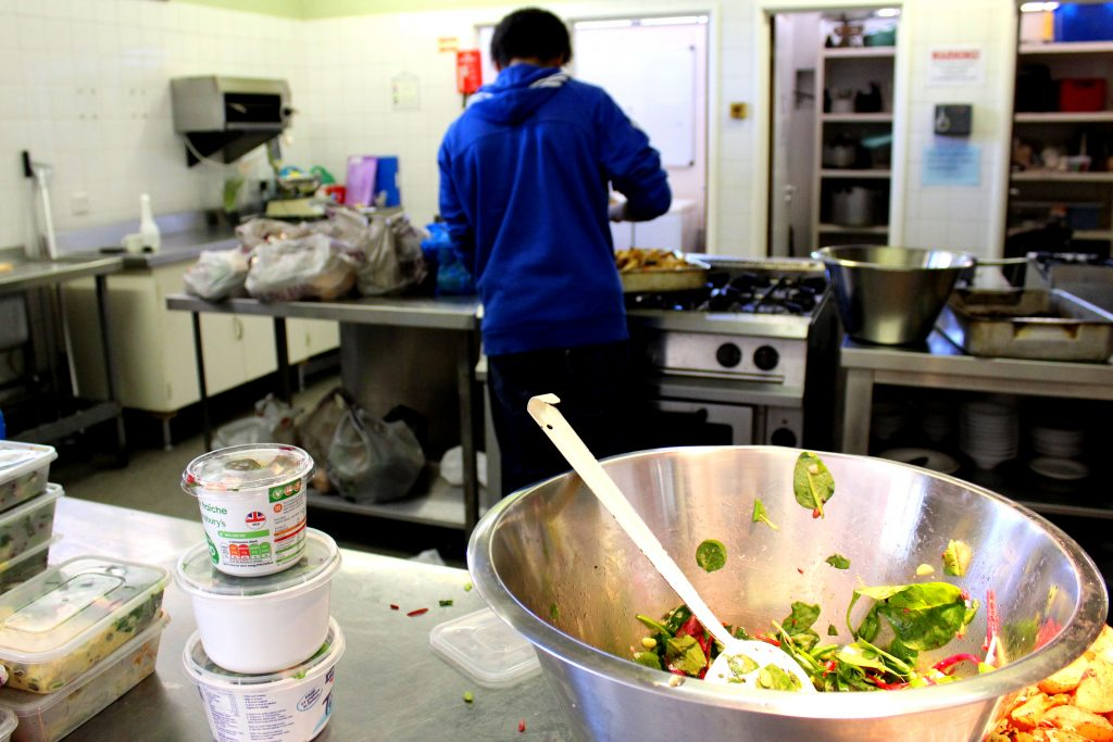 Photo shows salad bowl with a bit left over in the bottom of the bowl and a volunteer tidying up in the background of the kitchen.