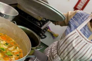 Chef Marcia lifts the lid off a large saucepan to reveal a colourful vegetable stew.
