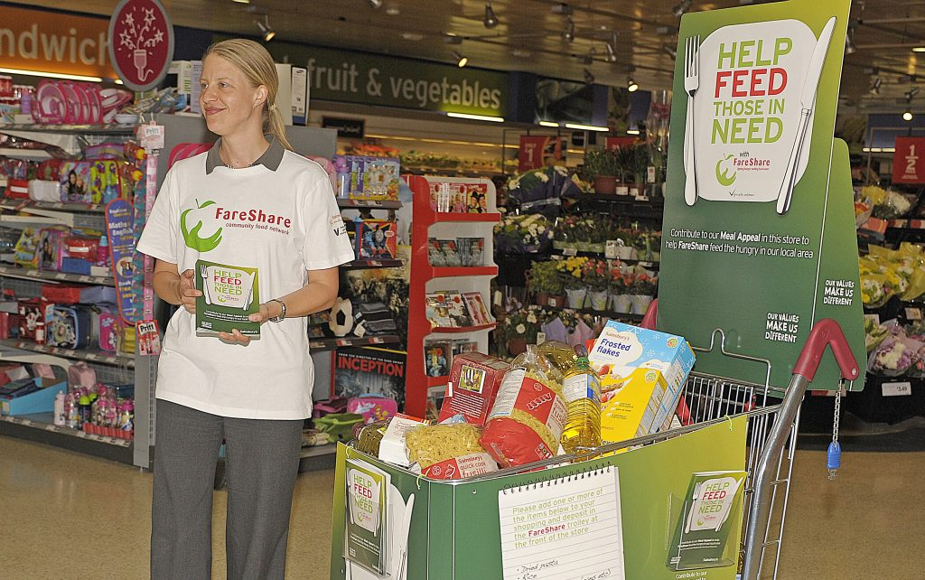 FareShare volunteer standing by a trolley of food in Sainsbury's