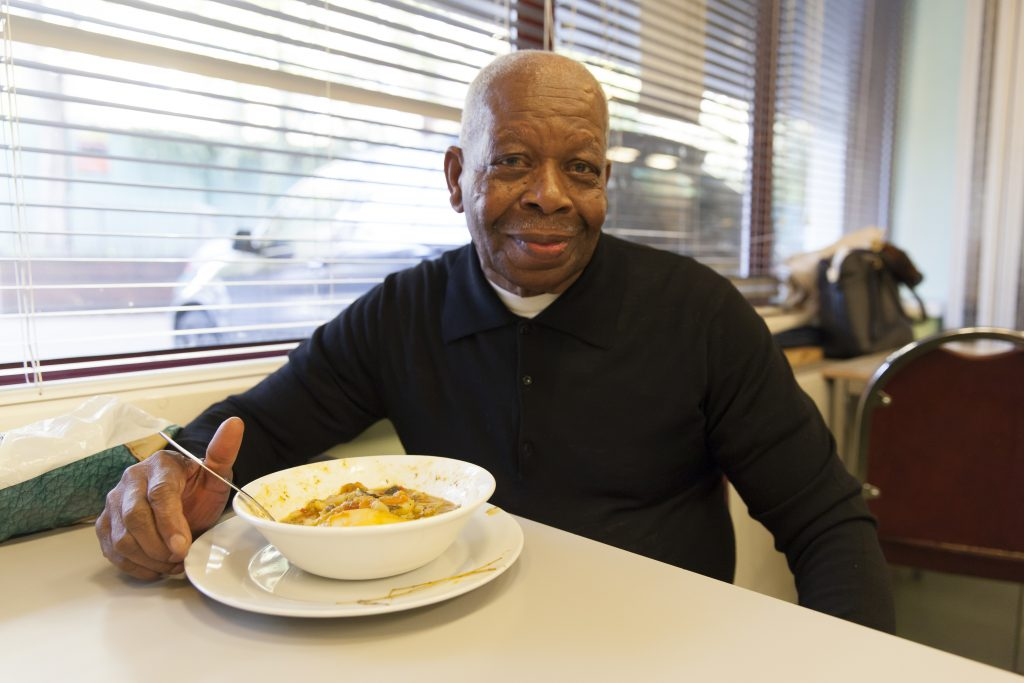 An older man smiles to the camera with a bowl of vegetable stew, made out of surplus food, in front of him.