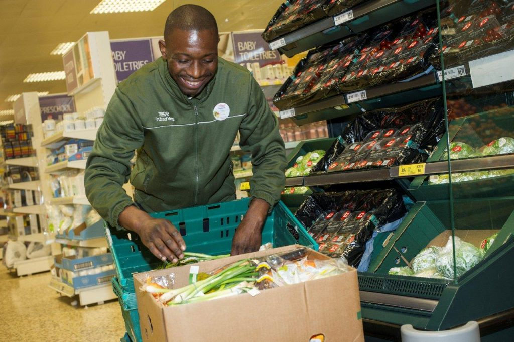 A smiling Tesco colleague in store with a box of veg