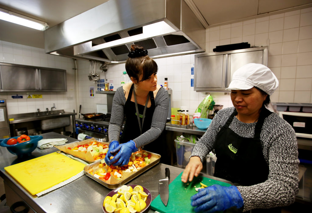 May0080973. The Daily Telegraph. Layla, the catering manager (left) and Fely (right), a service user, are seen preparing food in the kitchen of The Marylebone Project, a women's refuge, in Marylebone, London, which benefits from the charity Fare Share. Excess food from supermarkets is distributed by the charity Fare Share to needy people such as the service users of the Marylebone Project, many of whom are vulnerable and homeless women. Fare Share is the UK's largest charity fighting hunger and food waste, and is one of this year's Telegraph Christmas Charity Appeal chosen charities. Tuesday January 16, 2018.
