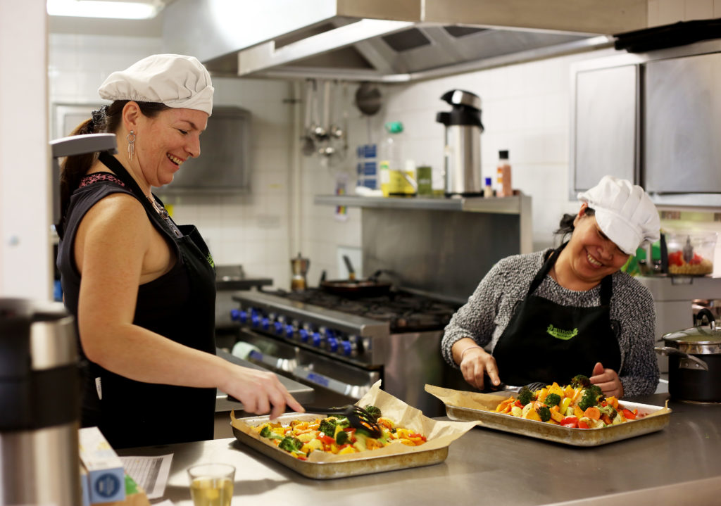 MaMay0080973. The Daily Telegraph. Fely, a service user (right) and Tanya, an ex-service user (left), are seen preparing food in the kitchen of The Marylebone Project, a women's refuge, in Marylebone, London, which benefits from the charity Fare Share. Excess food from supermarkets is distributed by the charity Fare Share to needy people such as the service users of the Marylebone Project, many of whom are vulnerable and homeless women. Fare Share is the UK's largest charity fighting hunger and food waste, and is one of this year's Telegraph Christmas Charity Appeal chosen charities. Tuesday January 16, 2018.