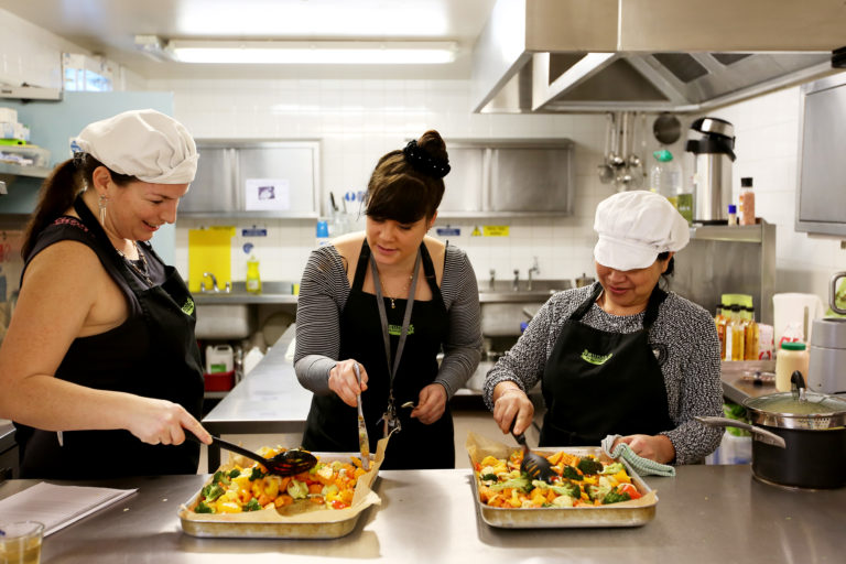 MaMay0080973. The Daily Telegraph. Fely, a service user (right) and Tanya, an ex-service user (left), are seen being taught to prepare food by catering manager Layla (centre) in the kitchen of The Marylebone Project, a women's refuge, in Marylebone, London, which benefits from the charity Fare Share. Excess food from supermarkets is distributed by the charity Fare Share to needy people such as the service users of the Marylebone Project, many of whom are vulnerable and homeless women. Fare Share is the UK's largest charity fighting hunger and food waste, and is one of this year's Telegraph Christmas Charity Appeal chosen charities. Tuesday January 16, 2018.